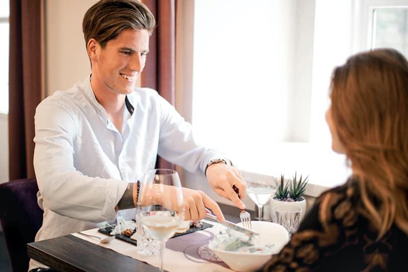 Ein Mann und eine Frau essen zusammen bei einem Date im Restaurant
