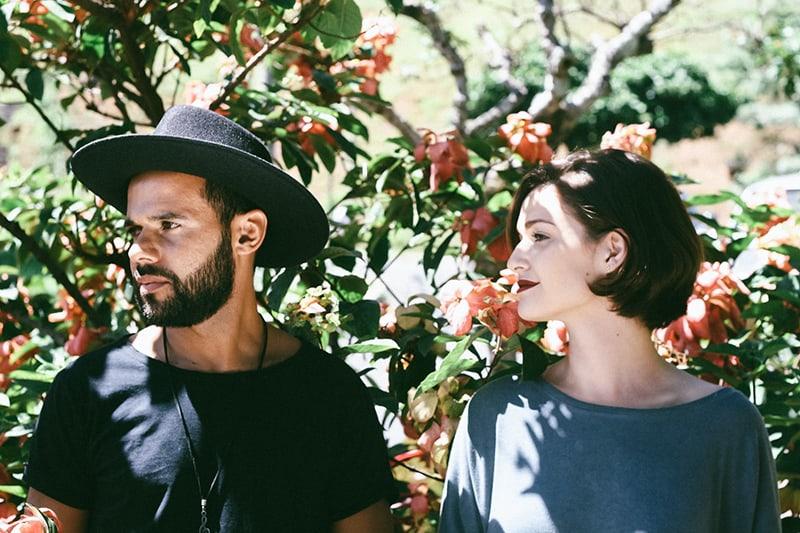 Ein Mann und eine Frau schauen beiseite, während sie in der Nähe der Pflanzen stehen
