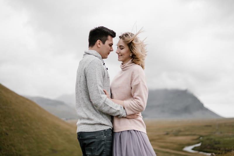 ein Mann und eine Frau sehen sich an im Stehen in der Natur