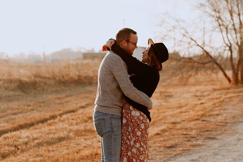 Ein Mann und eine Frau umarmen sich, während sie in der Nähe des Feldes stehen