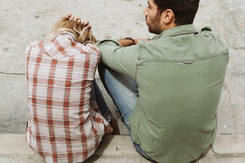 ein Mann und eine traurige Frau eine Frau, die am Bordstein sitzt