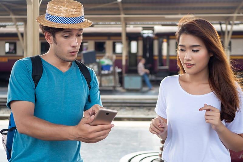 Ein Mann zeigt ein Smartphone einer Frau, während er sich seltsam verhält