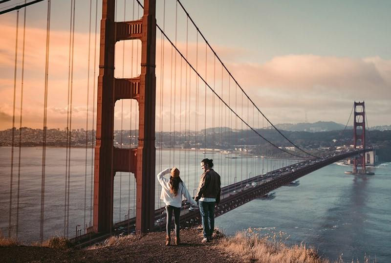 ein Paar Händchen haltend, während es in der Nähe der Golden Gate Bridge steht und den Sonnenuntergang beobachtet