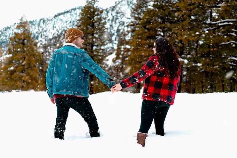 ein Paar, das sich ansieht, während es Hände hält und im Schnee steht