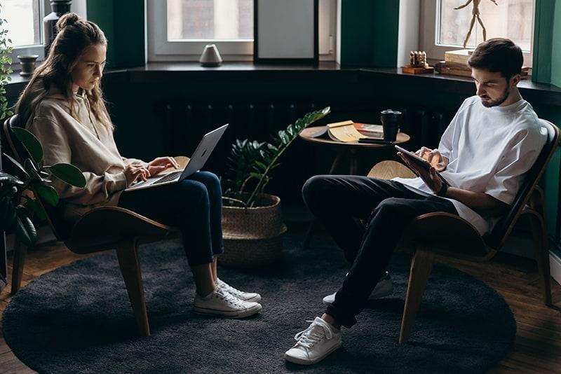 ein Paar benutzt ihre Geräte und ignoriert sich gegenseitig