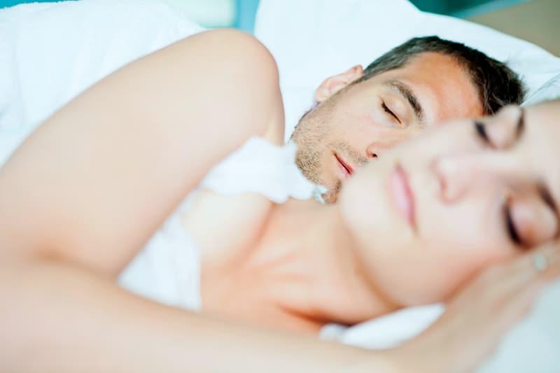 Ein Paar schläft in einem Bett mit weißen Laken