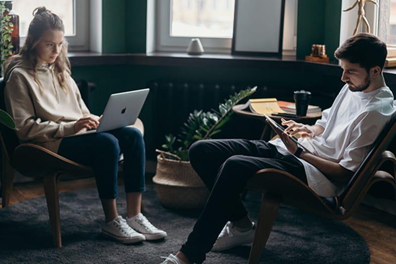ein Paar sitzt auf den Stühlen während beide mit ihrem Gerät beschäftigen