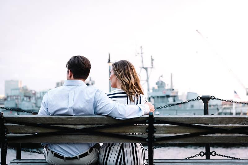 Ein Paar sitzt auf der Bank in der Nähe des Gewässers und redet