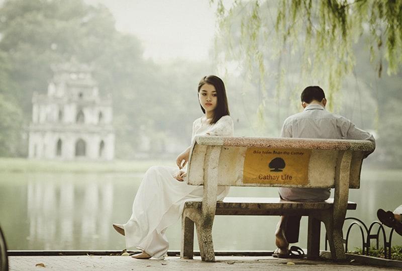 ein Paar sitzt nach der Trennung getrennt auf der Bank