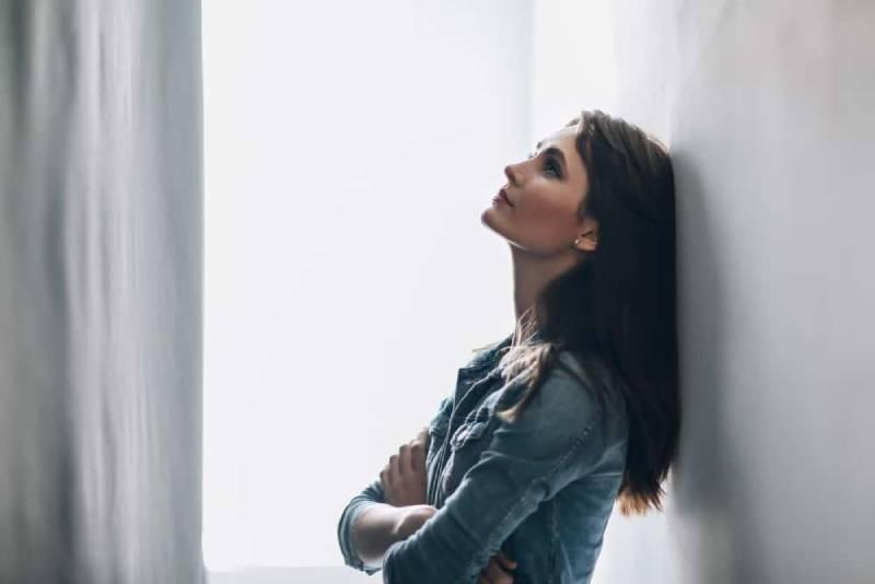 ein Porträt einer traurigen Frau die an eine Wand gelehnt ist