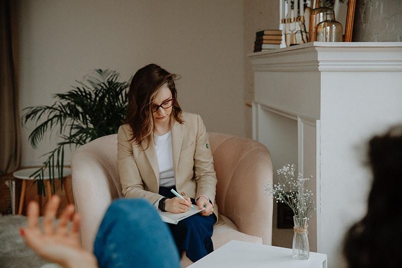 Ein Therapeut macht sich Notizen, während er dem Klienten zuhört