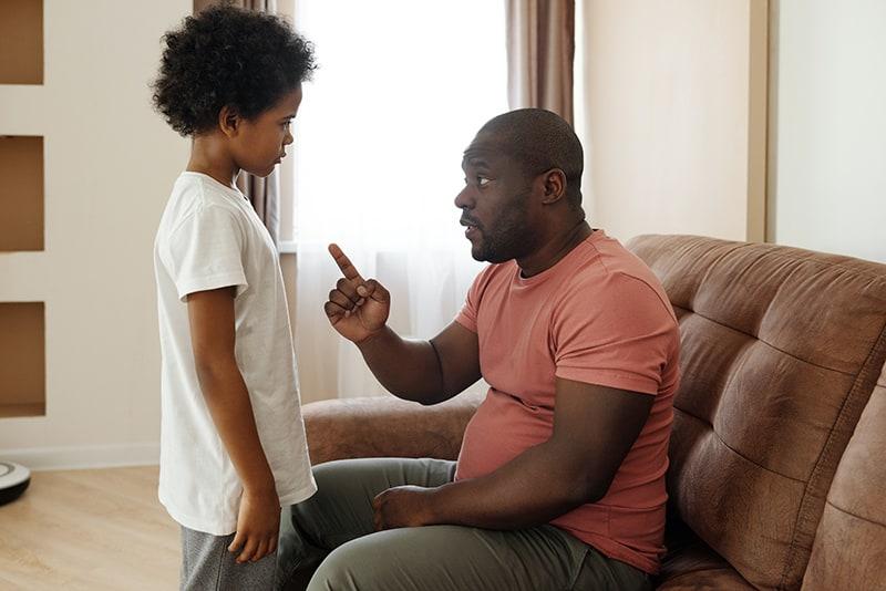 Ein Vater spricht mit seinem Sohn, während er auf der Couch sitzt und mit einem Finger zeigt