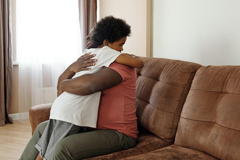 Ein Vater umarmte seinen Sohn, während er auf dem Sofa saß