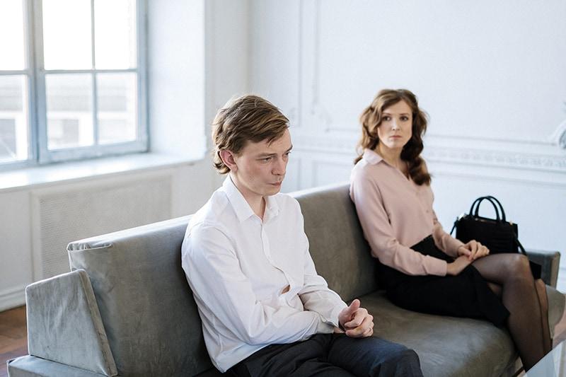 ein beleidigter Mann, der während eines Gesprächs mit einer besorgten Frau auf der Couch sitzt