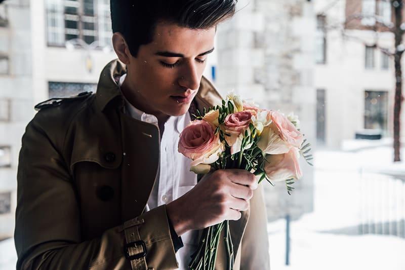 Ein charmanter Mann, der einen Strauß Rosen hält, während er im Gebäude steht