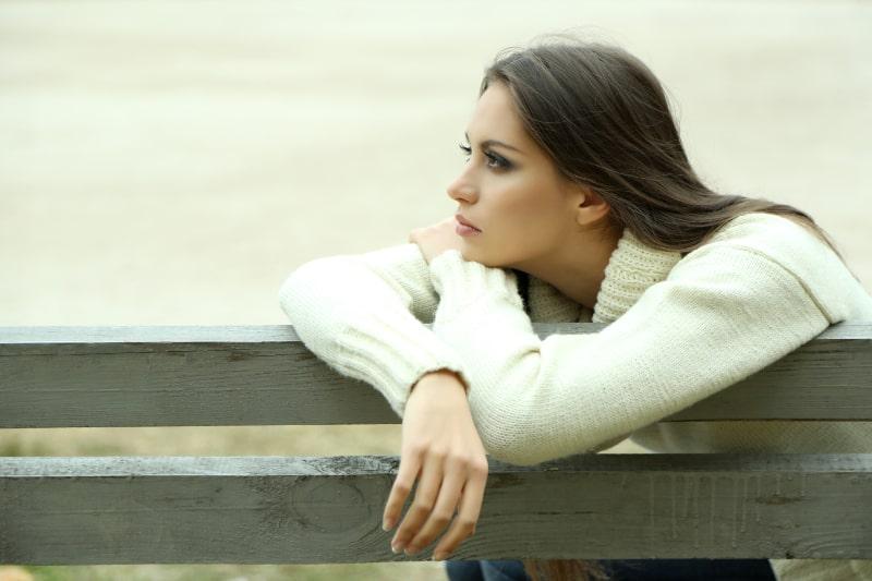 ein einsames Mädchen auf einer Parkbank