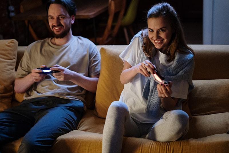 ein glückliches Paar, das Videospiele spielt, während es auf der Couch sitzt