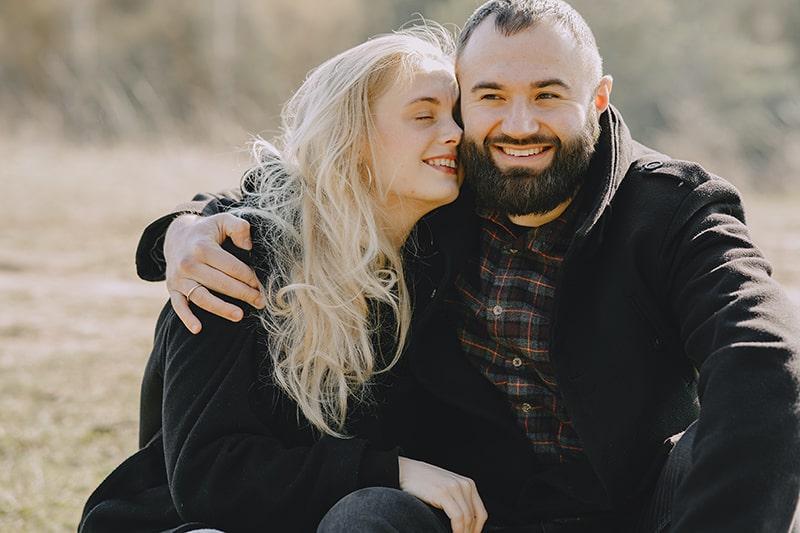 Ein glückliches Paar, das sich umarmt und lächelt, während es auf dem Feld sitzt