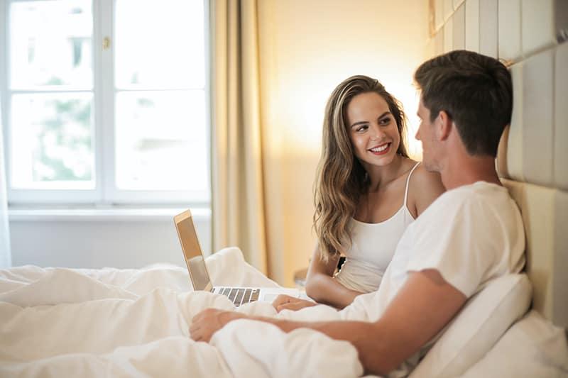 Ein glückliches Paar sitzt im Bett und spricht über ihre Pläne