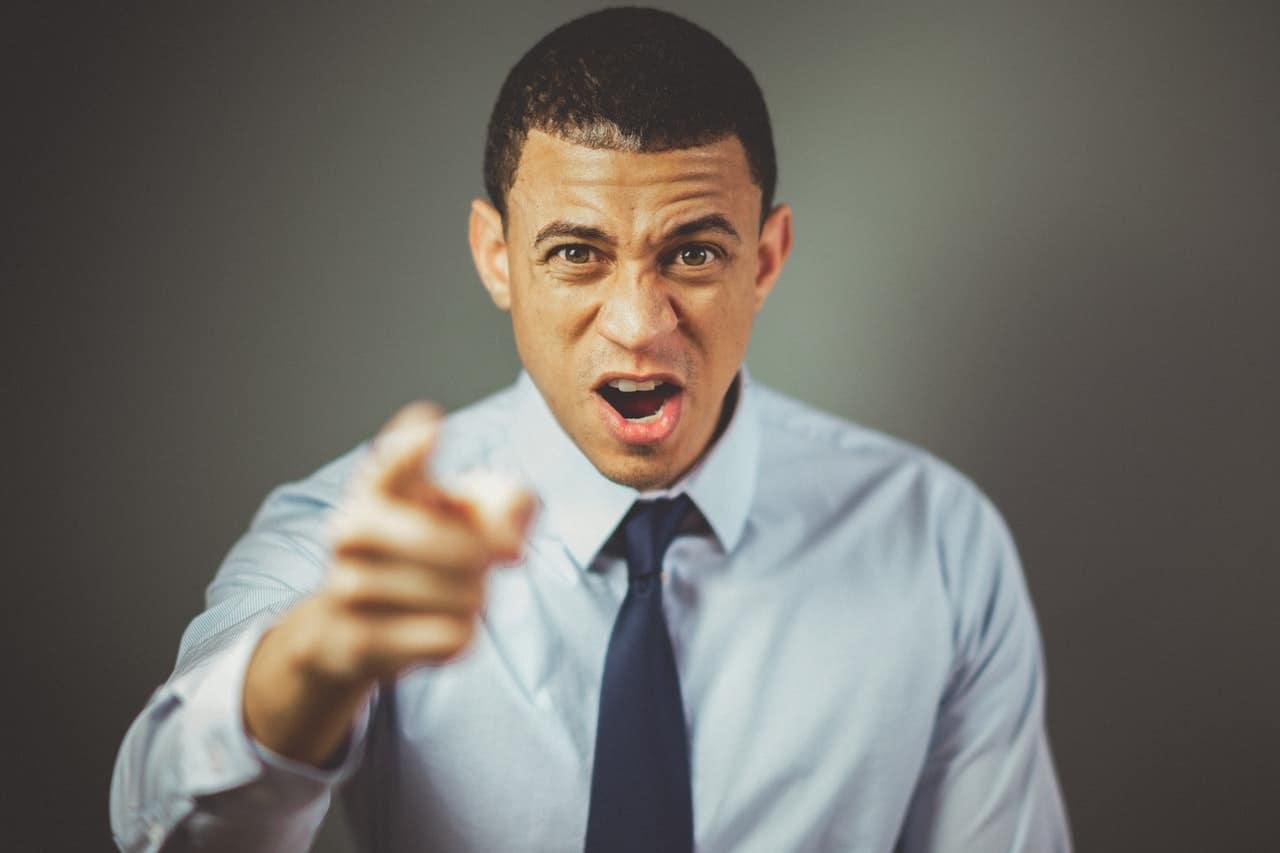 ein impulsiver Mann, der mit einem Finger schreit und zeigt