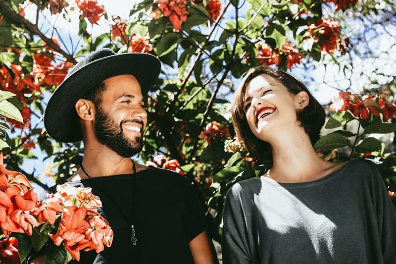 ein lächelnder Mann, der eine lächelnde Frau schaut, während er in der Nähe von Blumenbäumen steht