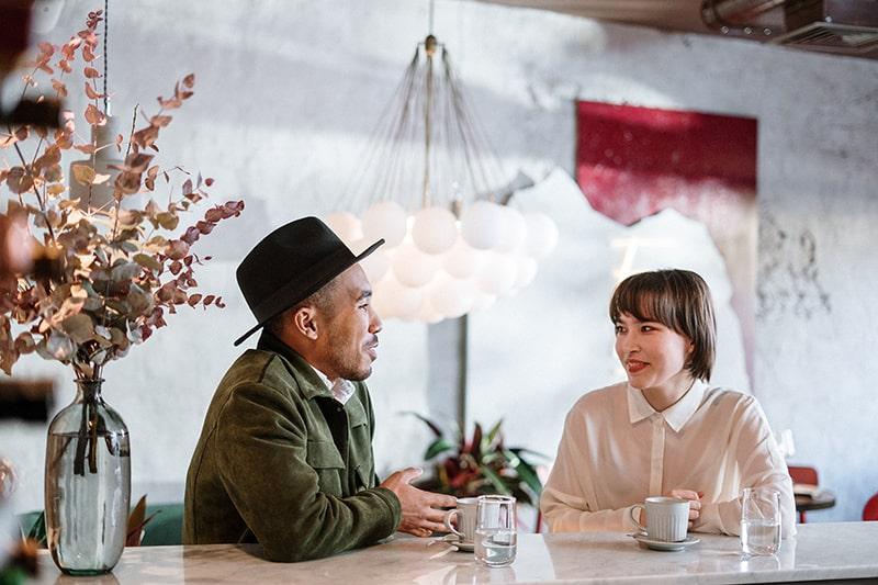 ein lächelndes Paar, das in der Cafeteria miteinander spricht