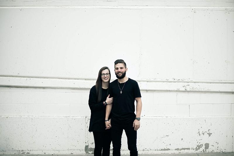 ein liebendes Paar, das Hände hält, während es nahe weißer Wand steht
