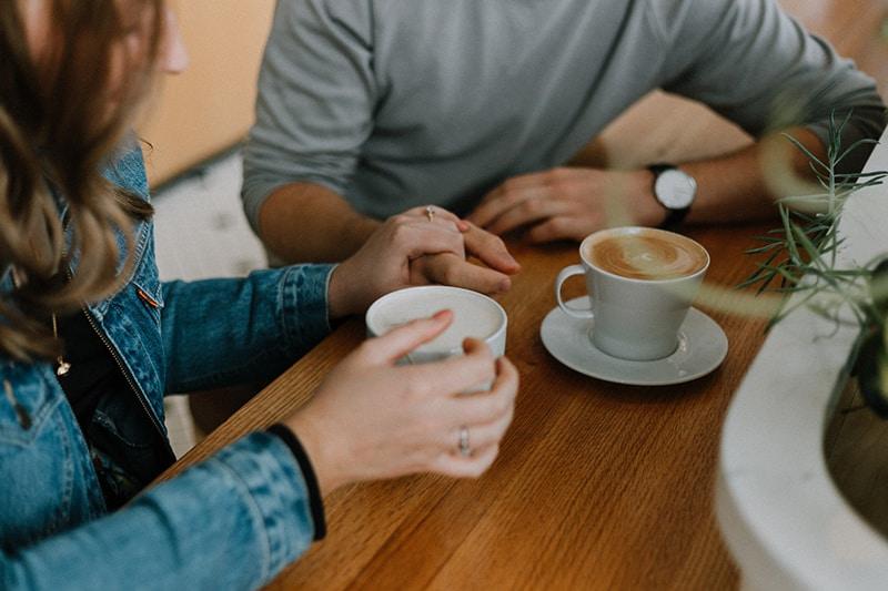 ein liebendes Paar, das Hände hält, während es Kaffee am Tisch trinkt