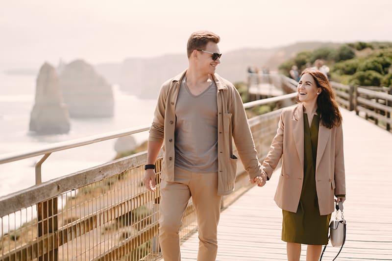 ein liebendes Paar, das beim gemeinsamen Gehen Hände hält