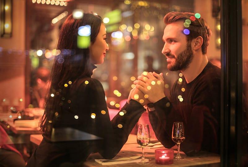 ein liebevolles Paar, das sich an den Händen hält, während es sich im Restaurant ansieht