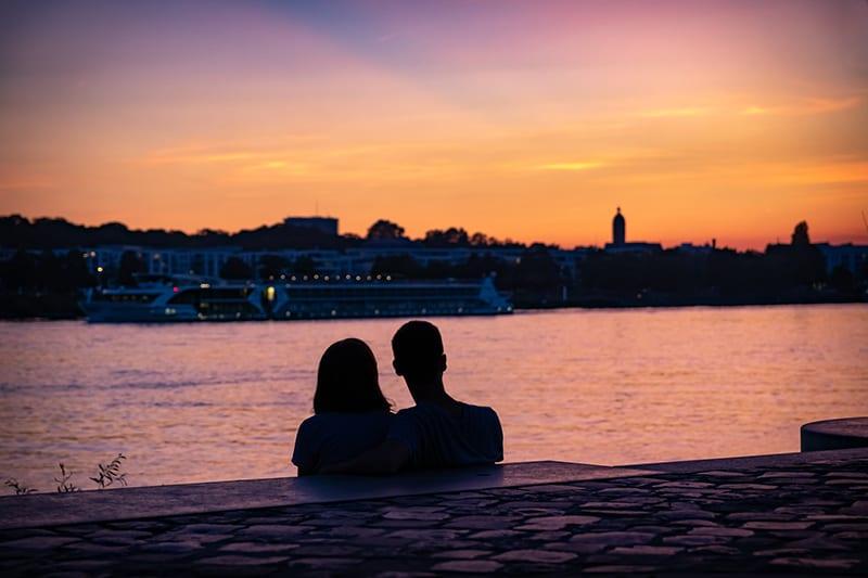 ein liebevolles Paar, das am Strand sitzt und einen Sonnenuntergang beobachtet