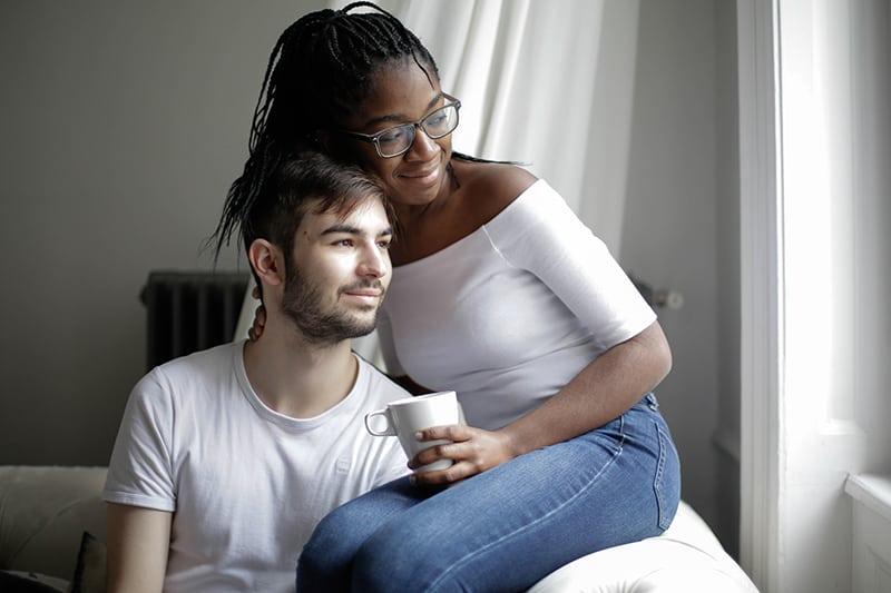 ein liebendes Paar, das auf der Couch sitzt, während Frau einen Mann umarmt und durch das Fenster schaut
