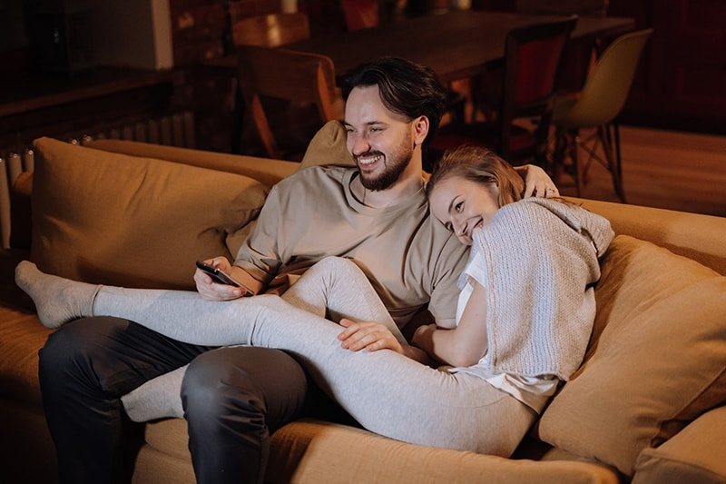 ein liebendes Paar sitzt auf der Couch und lacht zusammen