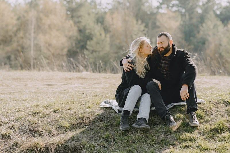 ein liebendes Paar sitzt auf einer Wiese und redet