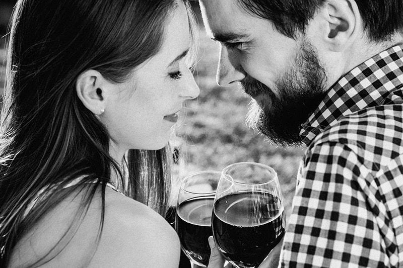 ein liebevolles Paar, das sich ansieht, während es ein Glas Wein hält