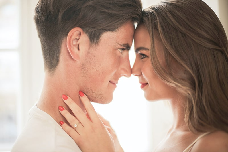 ein liebevolles Paar, das sich lächelnd gegenübersteht