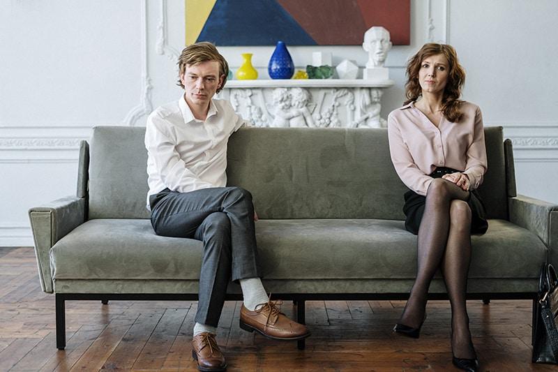 Ein nachdenklicher Mann und eine nachdenkliche Frau sitzen getrennt auf dem Sofa, während beide zur Seite schauen