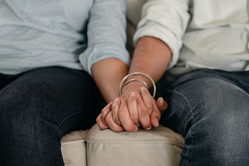 ein paar Händchen haltend auf dem Sofa sitzen