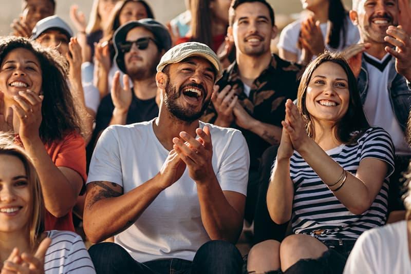 Ein Paar applaudiert im Stadion, während es in der Menge sitzt