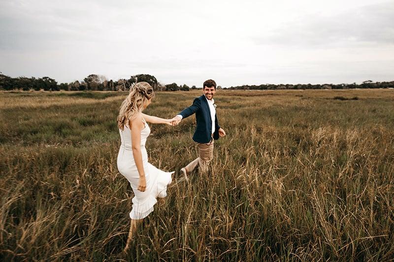 ein Paar, das auf der Wiese geht, während es Hände hält