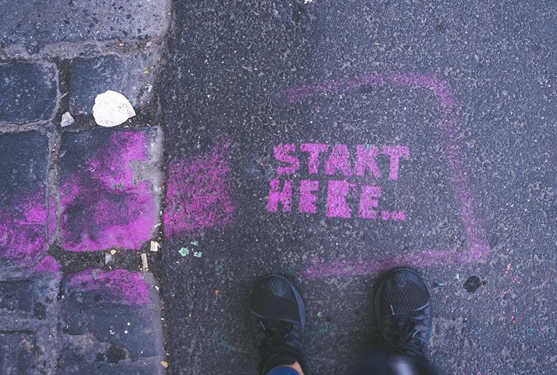 ein rosa Start Hier Text auf der Straße vor einer Person