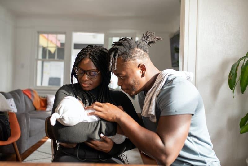 ein schwarzes Ehepaar, das ihr Baby ansieht