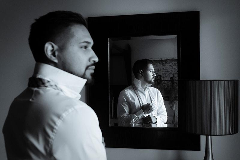 Ein selbstbewusster Mann, der in der Nähe des Spiegels steht und sein Hemd faltet