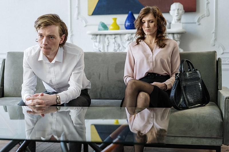 Ein trauriges Paar sitzt auf der Couch im Zimmer