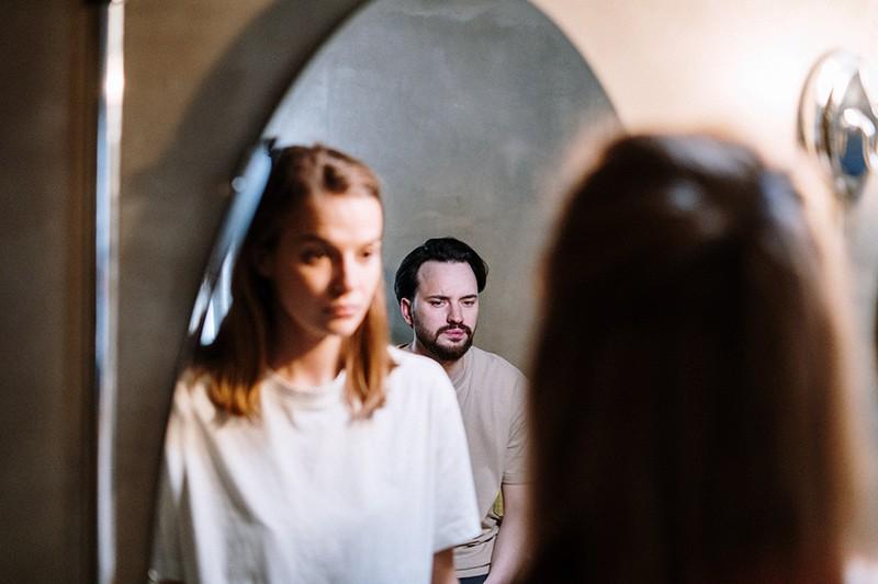 Ein verärgerter Mann sitzt hinter einer ernsten Frau, während sie vor dem Spiegel steht