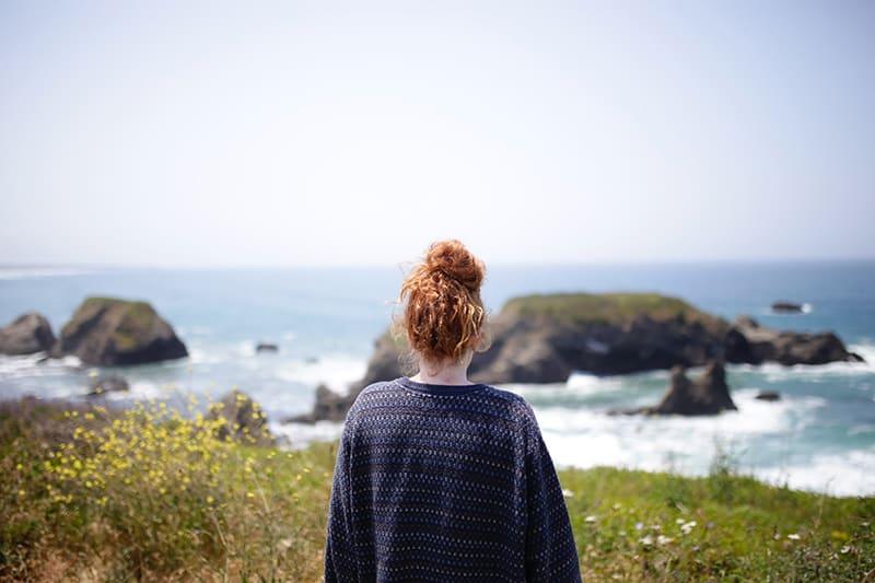 eine Frau, die allein steht und das Meer beobachtet