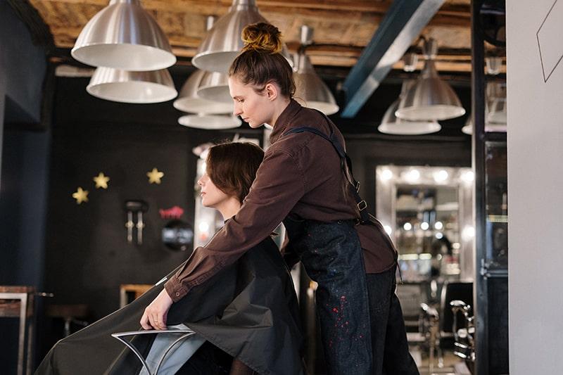 eine Frau bekommt einen Haarschnitt in einem Friseursalon