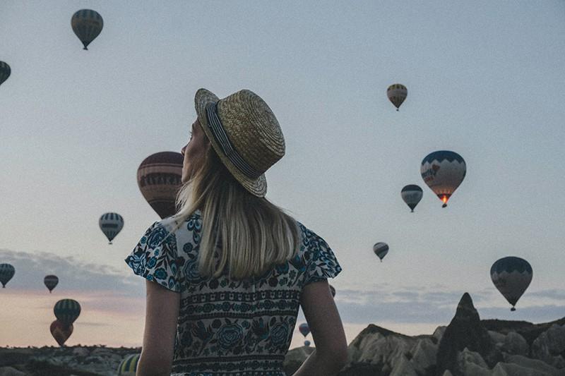 eine Frau, die Heißluftballons während des Sonnenuntergangs beobachtet