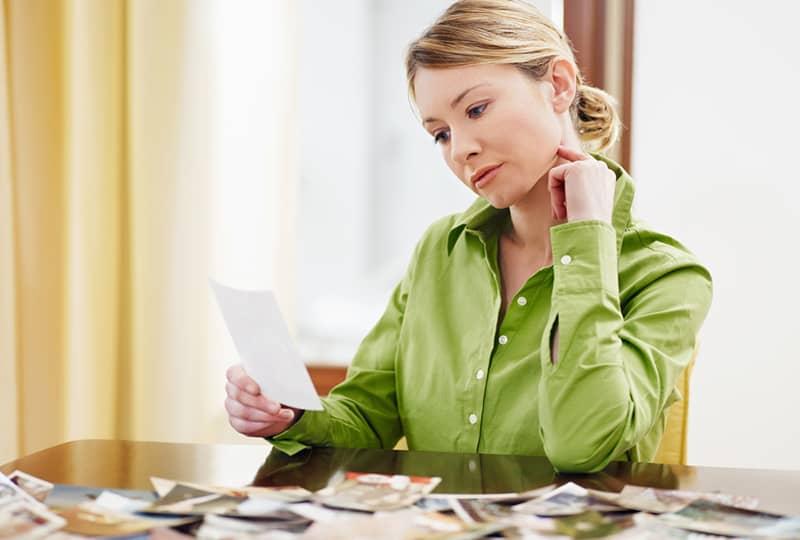 eine Frau, die Fotografie betrachtet, während sie am Schreibtisch sitzt