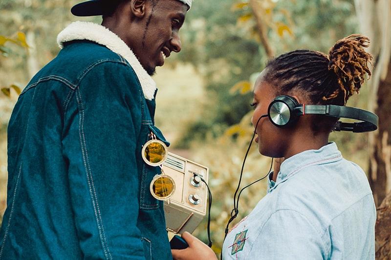 eine Frau, die Kopfhörer trägt, während sie neben einem Mann steht, der das Radio hält